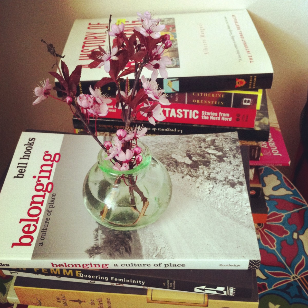 Two stacks of books, one in front of the other, one pile has a small clear flower vase with small pink flowers on top of it
