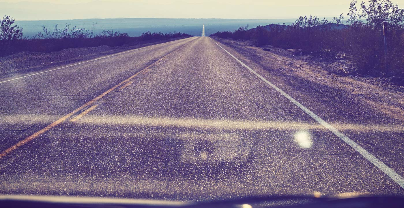 A long dry highway as seen through a windshield.