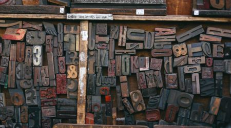 A well worn drawer of type sits with a wide range of individual type setting pieces sitting on it.
