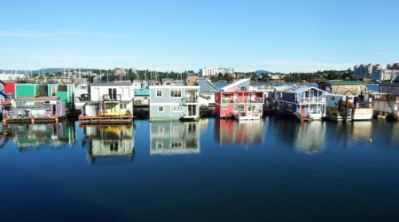 House boats rest on calm harbour waters at Fisherman's Wharf in Victoria, BC.