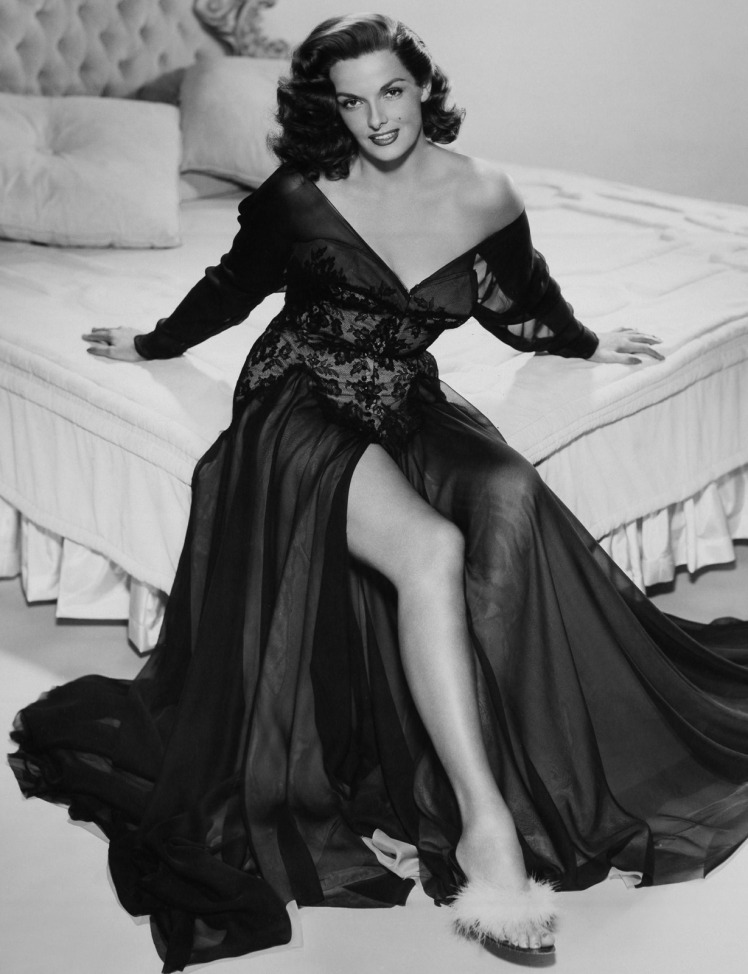 A famous actor (femme) sits on top of a bed wearing an amazing flowing gown, showing some leg.