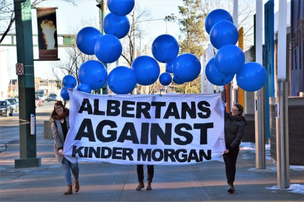 People walk down the sidewalk with baloons and a sign: Albertans against Kinder Morgan.