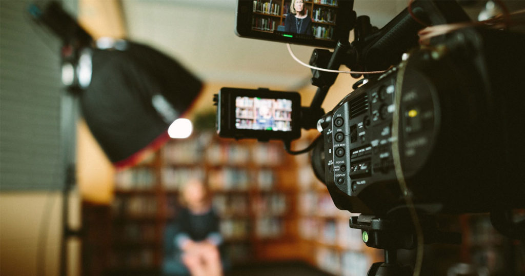 A video recorder makes a first pass at a woman speaking in a library, before massive edits.