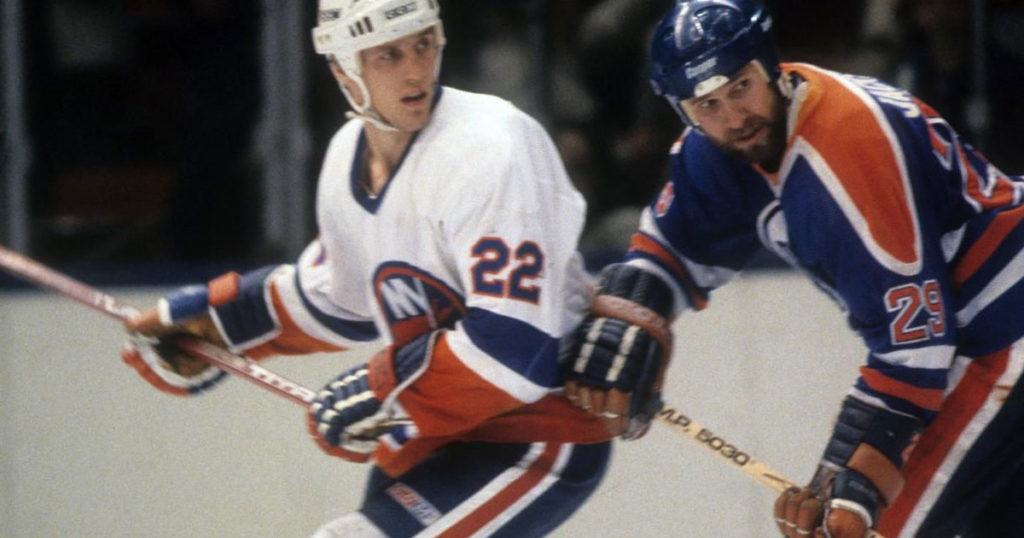 A New York Islander works over an Edmonton Oiler.